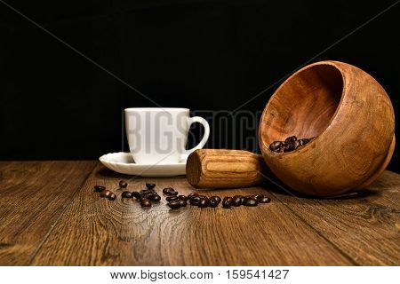 A cup of coffee coffee beans and mortar with pestle on the table