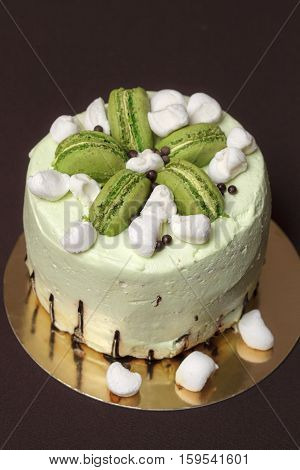 Green pistachio cake with strawberry mousse, macaroons and marshmallows, closeup