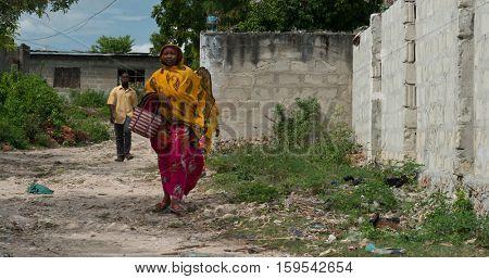 ZANZIBAR, TANZANIYA- JULY 13: people passing by in poor Zanzibar village on July 13, 2016 in Zanzibar