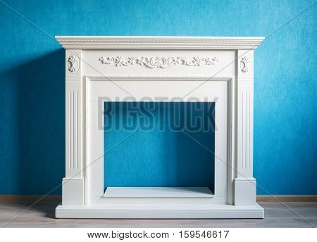 Beige portal for the electric fireplace. The picture was taken in the interior on the background wall of aqua color. The floor is light-colored laminate. Natural light from the window.