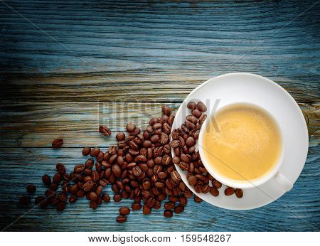 Coffee cup and coffee beans on old shabby wooden background.