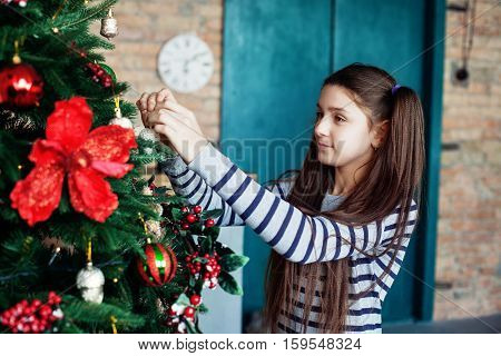 Beautiful teen girl decorates the Christmas tree in the house. The concept of Christmas and New Year.