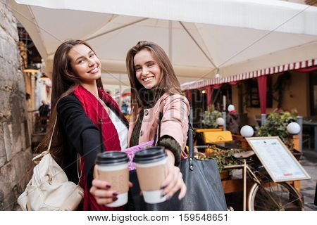 Two cheerful lovely young women standing and holding cups of coffee to go in old town