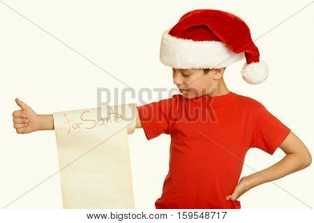 boy in red hat with long scroll wishes to santa - winter holiday christmas concept, yellow toned