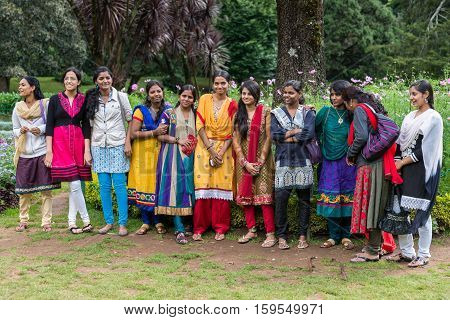 Nilgiri Hills India - October 25 2013: Colorful group of young Indian smiling college women posing in a row at the Ooty Botanical Garden. Bright colors of clothing against green background.