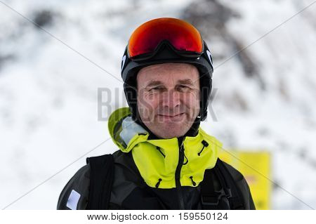 Close-up of happy male skier with large oversized ski goggles standing on the top of a mountain ready for skiing.