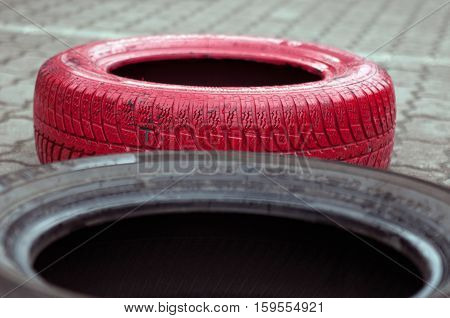 Black old tire and red painted tire.