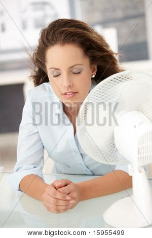 Young attractive woman sitting in office front of fan, feeling hot, cooling herself, eyes closed.?