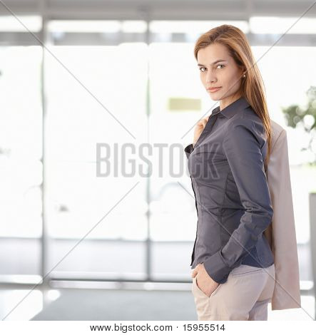 Young businesswoman leaving office, looking back at camera, smiling. Copy space on left.?
