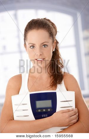 Pretty girl holding scale in hands, smiling, dieting.?