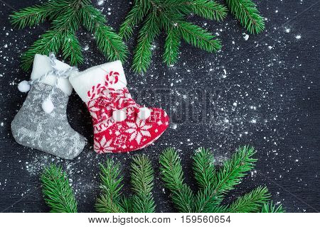 Christmas Stockings Pair On Snowbound Black Background With Fir Branches