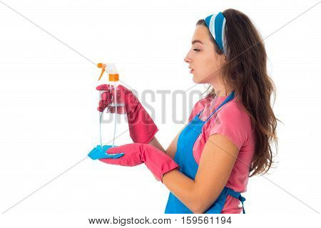 profile portrait of young maid woman in an apron with cleansers isolated on white background