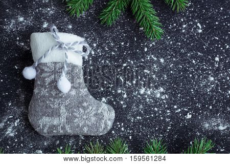 Grey Christmas Stocking On Snowbound Black Background With Fir Branches