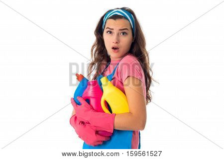 portrait of surprised maid girl in an apron with cleansers isolated on white background