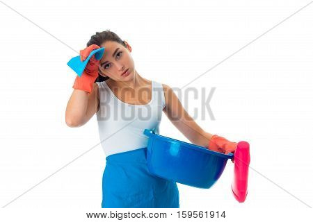 young tired maid woman in uniform with cleansers isolated on white background