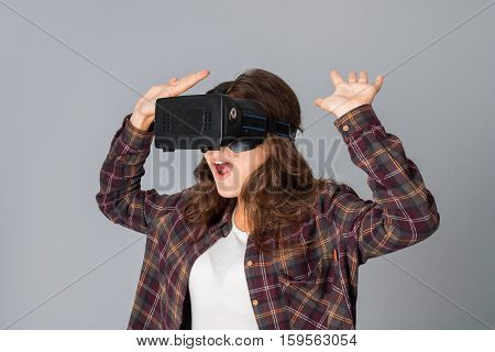 portrait of funny woman in virtual reality helmet in studio on grey background