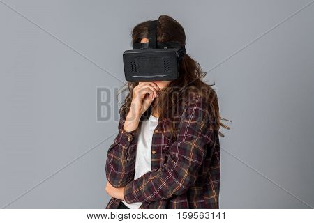young cute girl in virtual reality helmet in studio on grey background