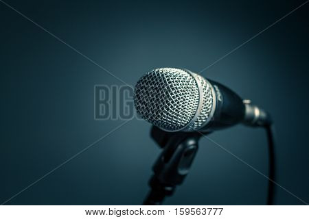 Microphone with metal body in holder isolated on dark background. Close-up selected focus