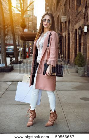 Fashionable model woman posing with shopping bags on city street
