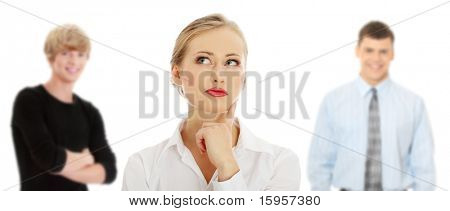 Thoughtful business woman looking right (making a choice) , isolated over a white background. Two young man in background