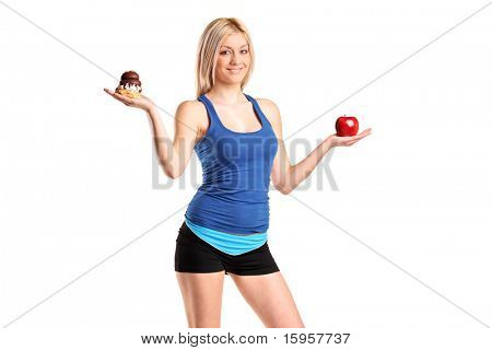 A woman holding an apple and slice of cake trying to decide which one to eat isolated against white background