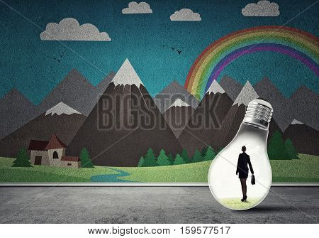 Businesswoman inside light bulb in room against nature drawn concept
