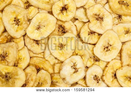 Banana chips dehydrated slices of fresh ripe bananas as food background.