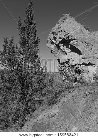 A jagged boulder sticking out of the side of a hill off of Lower Bridge Road in Central Oregon on a sunny spring afternoon.