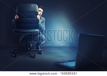Afraid businessman hidden behind a chair looks his laptop