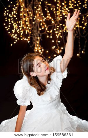 A young girl sits serenely in a white dress with closed eyes and arm extended up to heaven. She is worshiping in front of a starry background of Christmas lights.