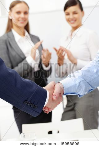 Photo of handshake of business partners after striking deal on background of two women applauding