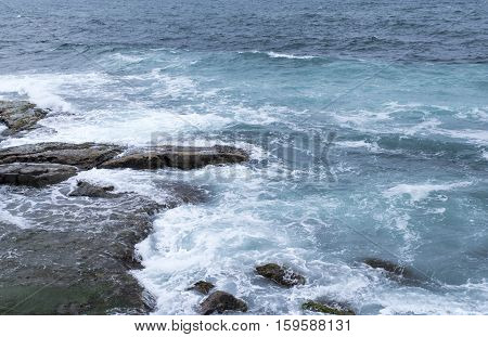 seascape, turquoise waters of the ocean beating on the coastal rocks