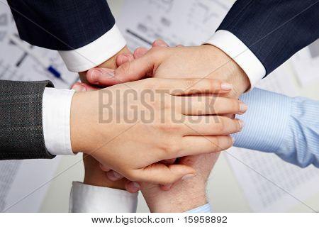 Imagen de socios de negocio las manos encima de uno al otro que simboliza la unidad y compañerismo