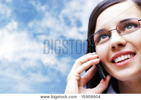 Photo of smart businesswoman talking by mobile phone with cloudy sky on background