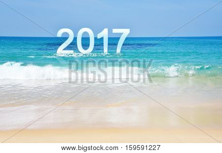 The Number 2017 standing on wave with Horizontal of clear blue sea and sky. Happy New Year conceptual image with copy space. The Number 2017 appear on wave.