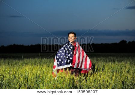 Smiling Man In A Wheat Field With American Flag