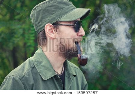 man with a pipe in uniform on a background of trees