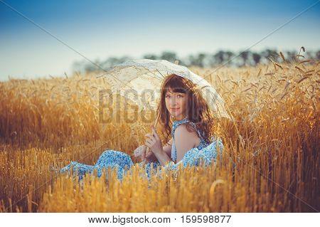Girl Sitting In Wheat Field Under A White Sun Umbrella