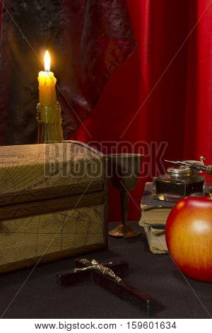 Old book a crucifix a casket and a burning candle on a table covered with a black cloth