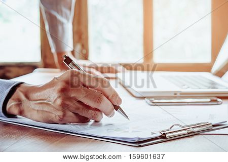 Business man hand working and writing business graph or analysis chart.Close up with sun flare.Business concept