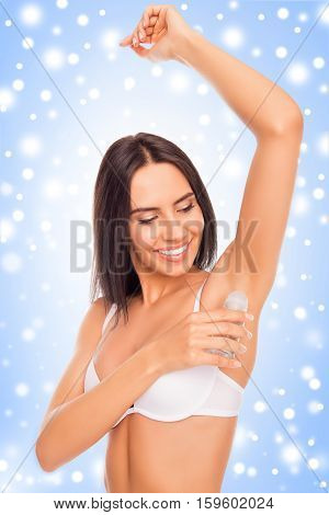 Happy Woman Putting Deodorant On Her Armpit On The Background Of Snowflakes