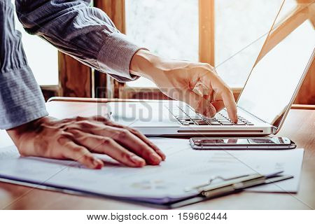 Business man hand using and working with laptop on office desk table close up.Business concept.