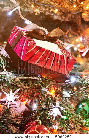 gift red colourfull box on christmas tree with blurred light