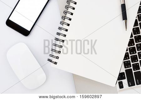 Modern White office desk table with laptop computer blank screen smart phone pen mouse and notebook. Top view with copy space.