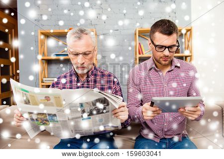 Old Father Reading Newspaper And His Son Using Tablet On Winter Background