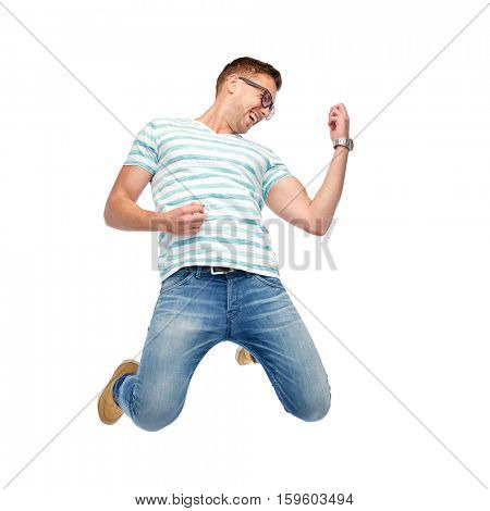motion, fun and people concept - happy young man jumping in air and playing imaginary guitar