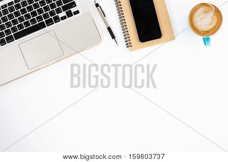 Modern White office desk table with laptop blank screen smart phone notebook pen and cup of coffee.Top view with copy space.Working desk table concept.