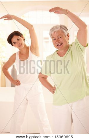 Healthy elderly woman doing exercises with personal trainer at home, smiling.