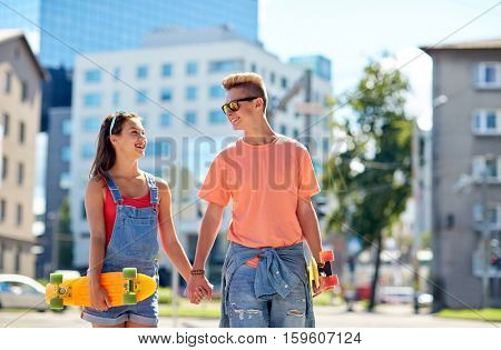 summer holidays, extreme sport and people concept - happy teenage couple with short modern cruiser skateboards on city street