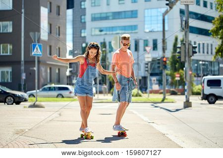 summer holidays, extreme sport and people concept - happy teenage couple riding short modern cruiser skateboards on city street